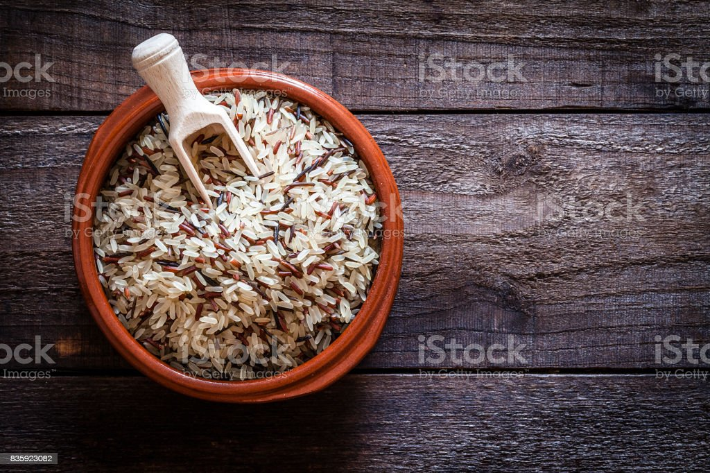 Brown bowl filled with mixed rice shot from above on rustic wooden table stock photo