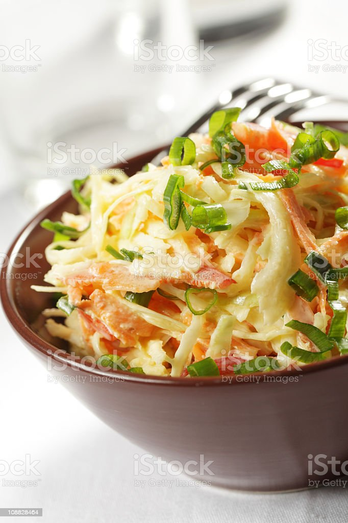 Brown bowl of coleslaw with bacon and a fork on a table stock photo