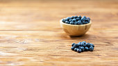Brown bowl with blueberries on table with copy space. Wooden dish with little fresh healthy berries on desk with space for text. Heap of small raw fruit rich in vitamin on wooden desk.