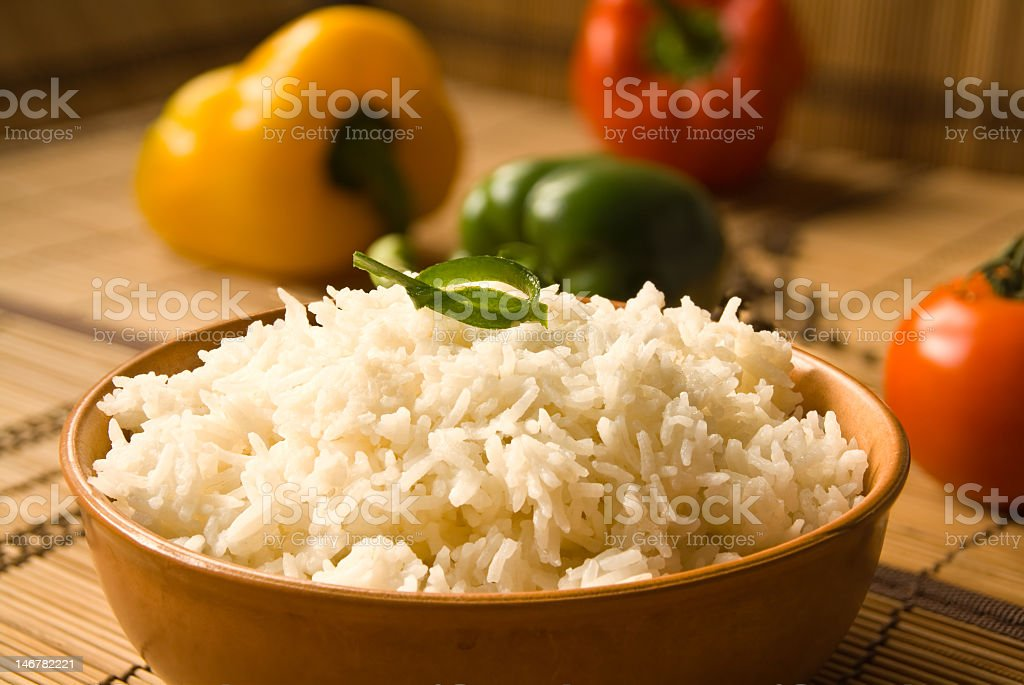 Brown bowl with rice on a table with fresh vegetables stock photo