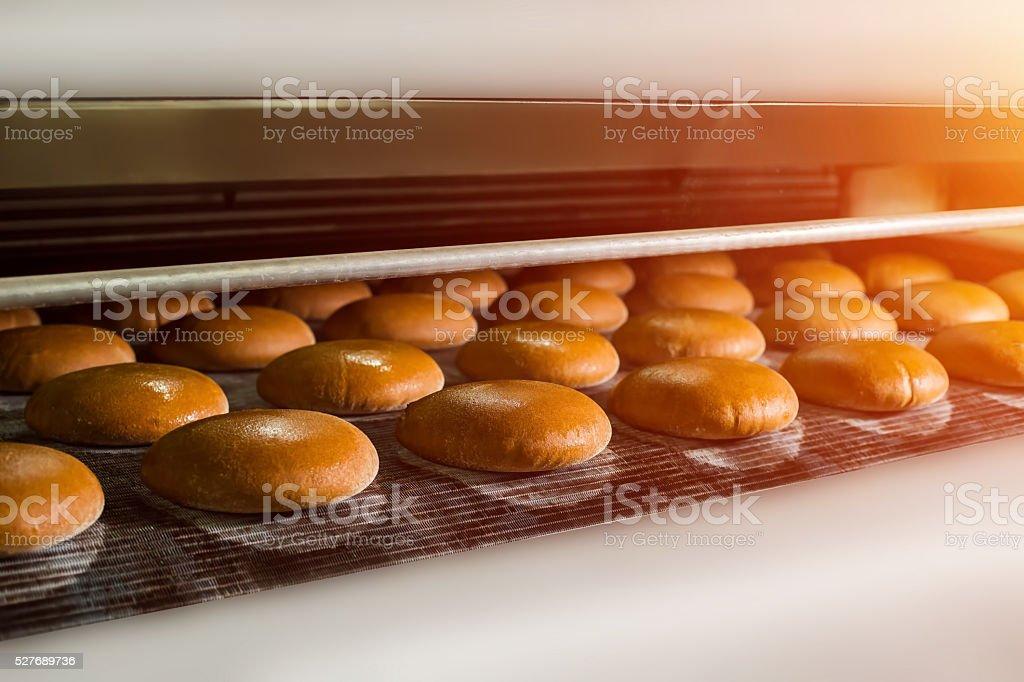 Brown bread loaves on conveyor. stock photo