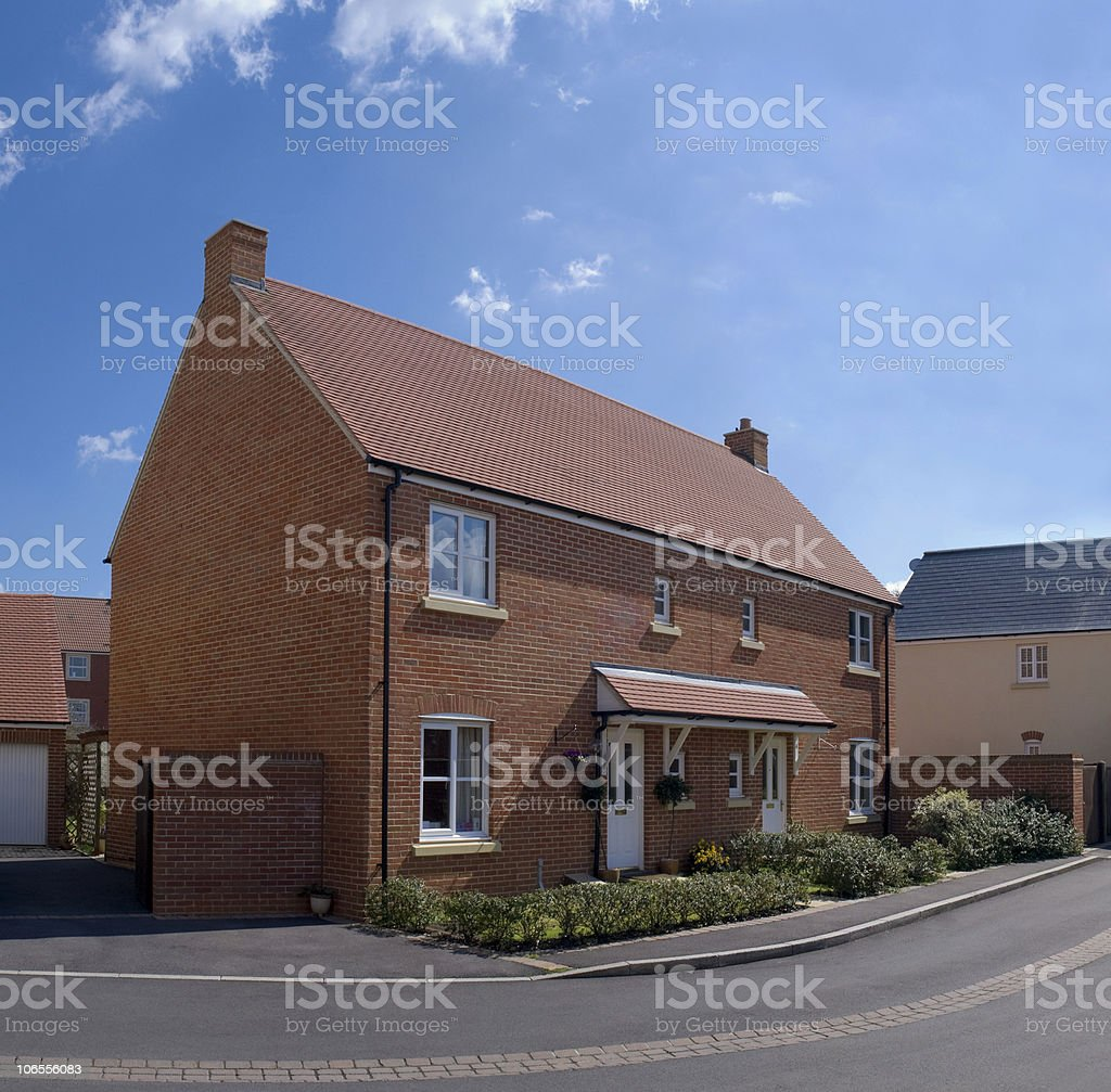 A brown bricked home that sits close to a two lane street royalty-free stock photo