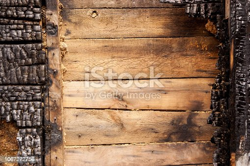brown burnt wall of house of wooden planks with embossed texture. background for copy space. concept of loss of real estate or home. property insurance.
