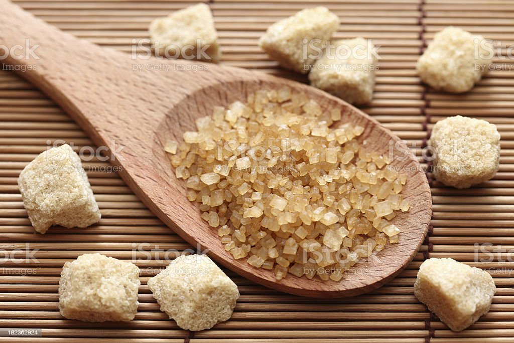 Brown cane sugar crystals in a wooden spoon stock photo
