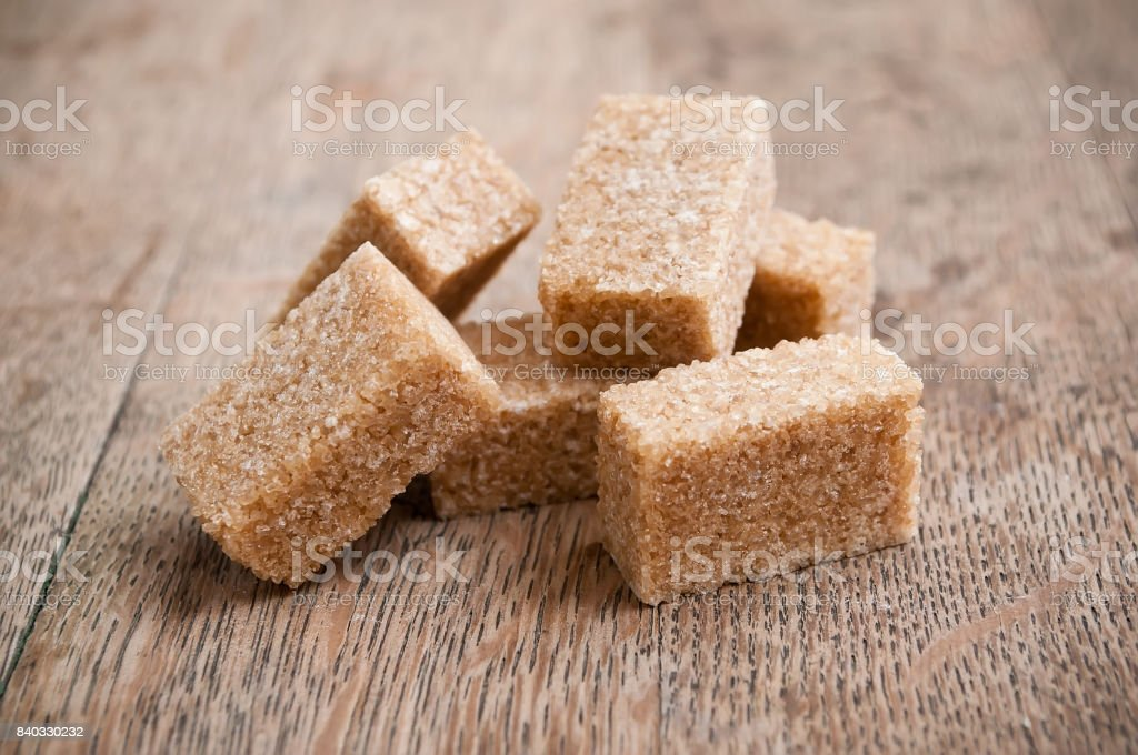 brown cane sugar cubes on wooden table stock photo