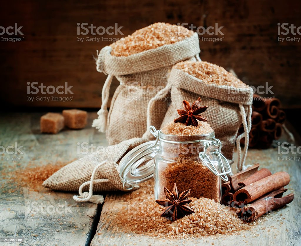 Brown cane sugar in bags made of burlap stock photo