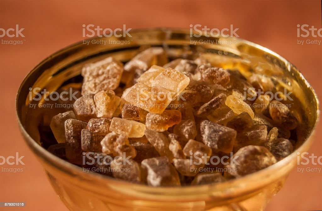 Brown cane sugar is lumpy inside the bowl of the golden cup. stock photo