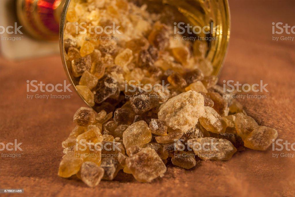 Brown cane sugar is poured out of the gold cup by pieces. stock photo