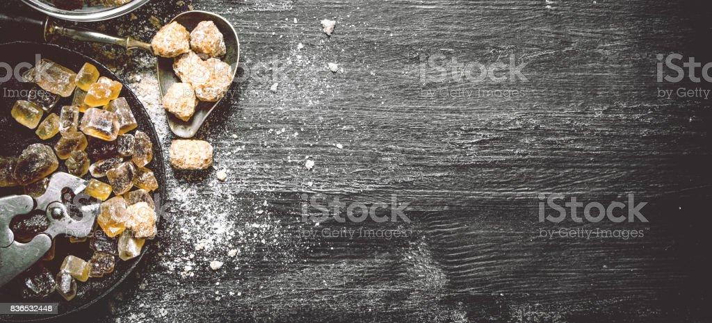 Brown cane sugar. On black rustic background. stock photo