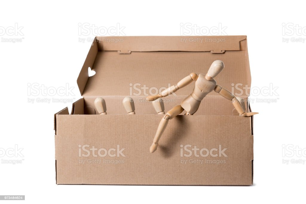 Brown cardboard box with wooden mannikins. One of them is coming out of it while others are sitting. Concept of thinking outside the box, leadership, freedom. stock photo