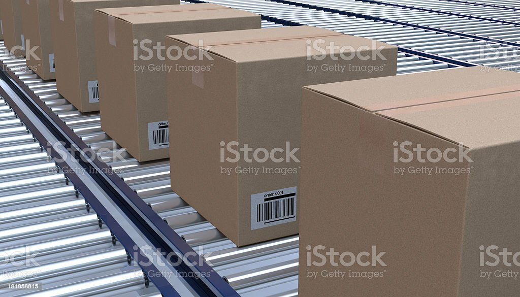 Brown cardboard boxes lined up on a conveyor belt stock photo