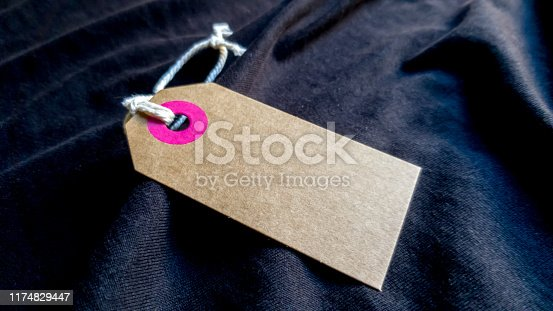 brown cardboard label with a thin cord on a black fabric background. Background, holiday concept