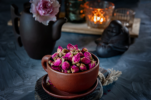 brown ceramic Cup of rosebud tea sits on a wooden table. Tea time, cozy atmosphere. Kitchen still life with tea from pink flowers with warm light in the background