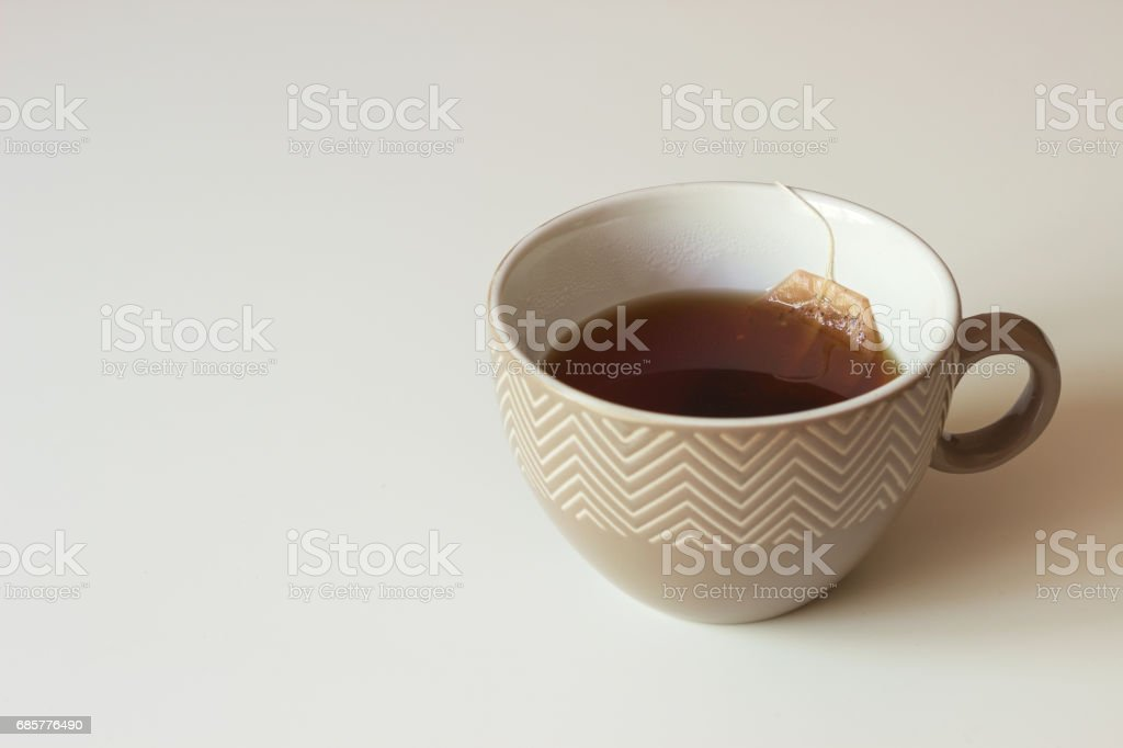 Brown ceramic cup with black tea and paper tea bags on table. royalty-free stock photo
