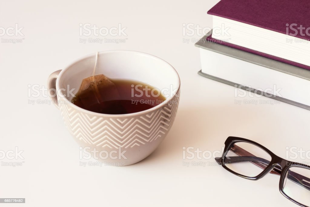 Brown ceramic cup with black tea and paper tea bags, Reading Glasses and books on table. royalty-free stock photo