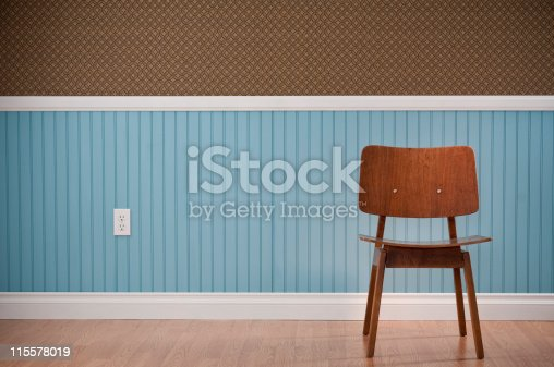 Brown Mid-Century Modern chair in empty room. The wall has a blue beadboard wainscoting and a patterned wallpaper.*