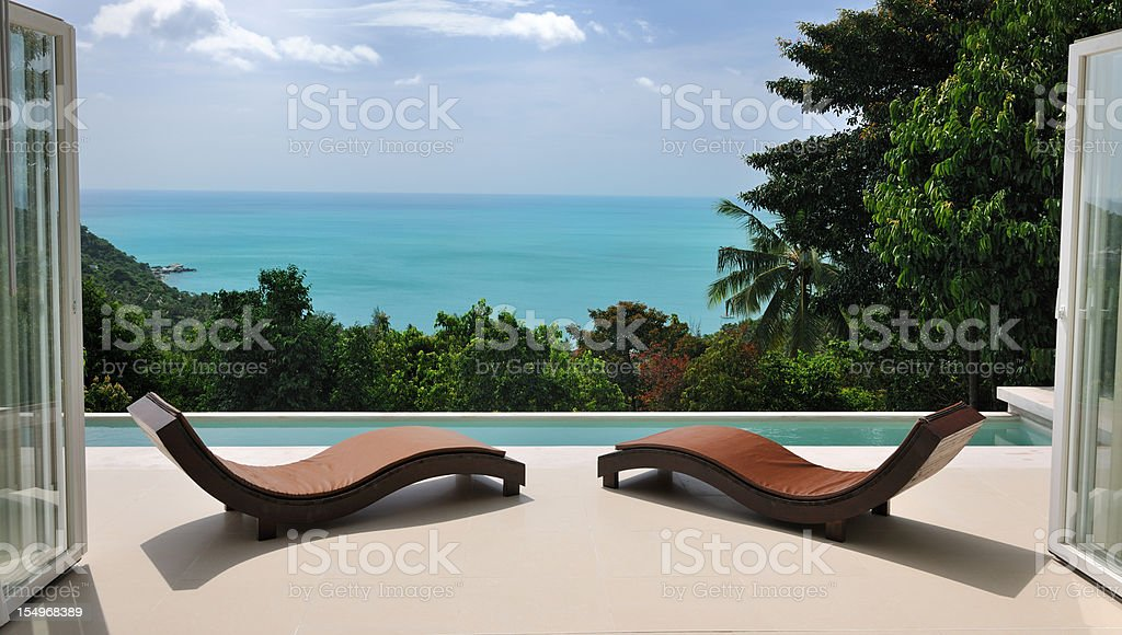 Brown chaise lounges at private pool villa stock photo