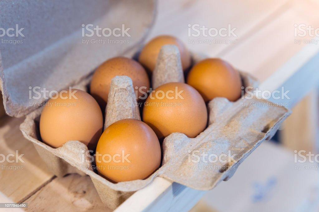 Brown chicken eggs in a brown carton box contain six eggs.