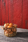 An old rusty wire basket full of freshly collected brown chicken eggs, the basket is sitting on an old weathered wood bench with a weathered red barn planks in the background. There is hay at the bottom of the basket to cushion the eggs.