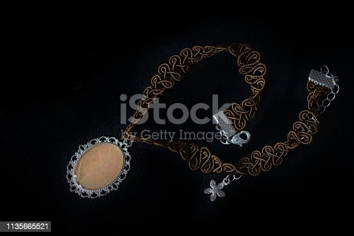 istock Brown choker with a maple leaf pendant on a dark background close up 1135665521
