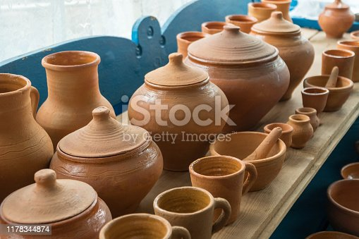 Brown clay pots made in ground oven with firewoods using old traditional ukrainian pottery technology. Local traditional craft and art concept