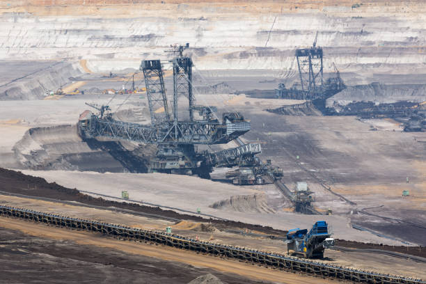 Brown coal open pit landscape with digging excavator in Germany Brown coal open pit landscape with enormous digging excavator in Garzweiler mine Germany tagebau stock pictures, royalty-free photos & images