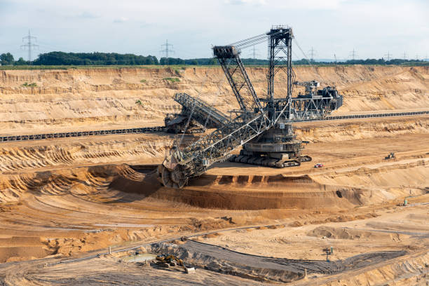 Brown coal open pit landscape with digging excavator in Germany Brown coal open pit landscape with enormous digging excavator in Hambach mine Germany, This machine is the biggest vehicle in the world tagebau stock pictures, royalty-free photos & images