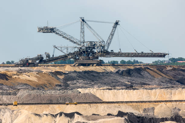 Brown coal open pit landscape with digging machine in Germany Brown coal open pit landscape with enormous digging machine in Garzweiler mine Germany tagebau stock pictures, royalty-free photos & images