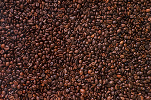 brown coffee beans background. - caffè foto e immagini stock