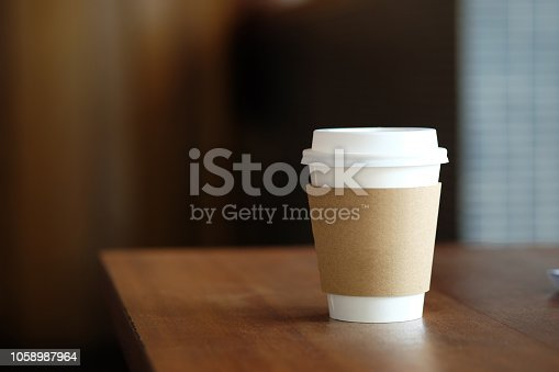 Coffee paper cup on wood table in coffee cafe.