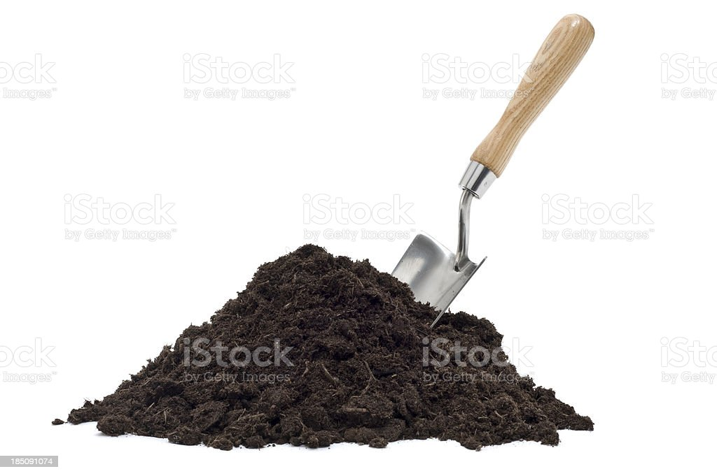 Brown compost pile with a spade on top stock photo