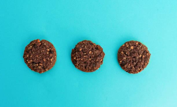 braune cookies auf hellblauem hintergrund - hausgemachte zuckerplätzchen stock-fotos und bilder