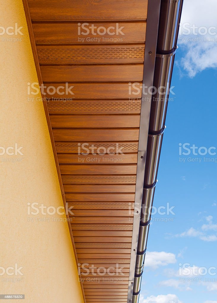 Brown copper gutter under a cloudy blue sky stock photo