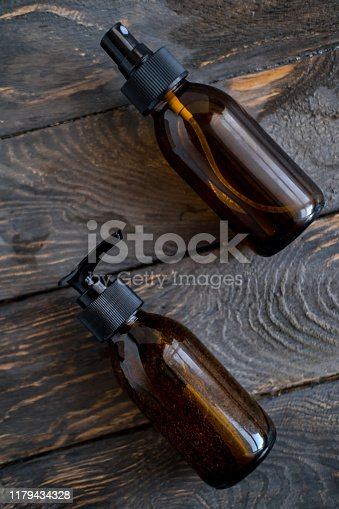 1167558793 istock photo Brown cosmetic bottles on wooden table flat lay 1179434328