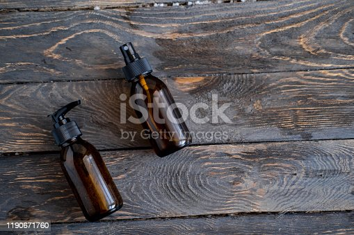 1167558793 istock photo Brown cosmetic bottles on wooden table flat lay 1190671760