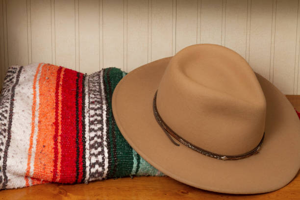 Brown cowboy hat with colorful Mexican blanket on a wooden table stock photo
