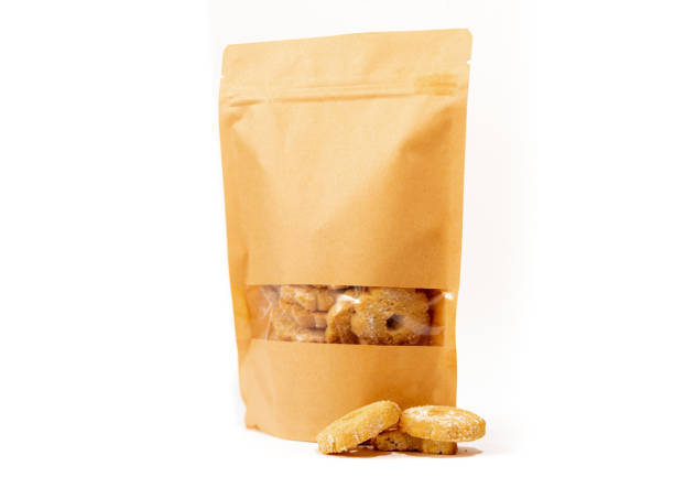 brown craft food packaging in paper, plain doypack standup bag filled with biscuits with window and zipper on white background stock photo