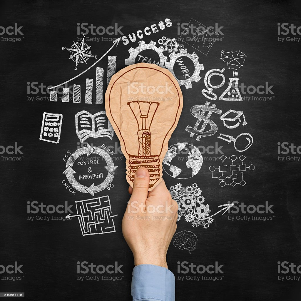 brown crumpled paper bulb on top of sketches stock photo