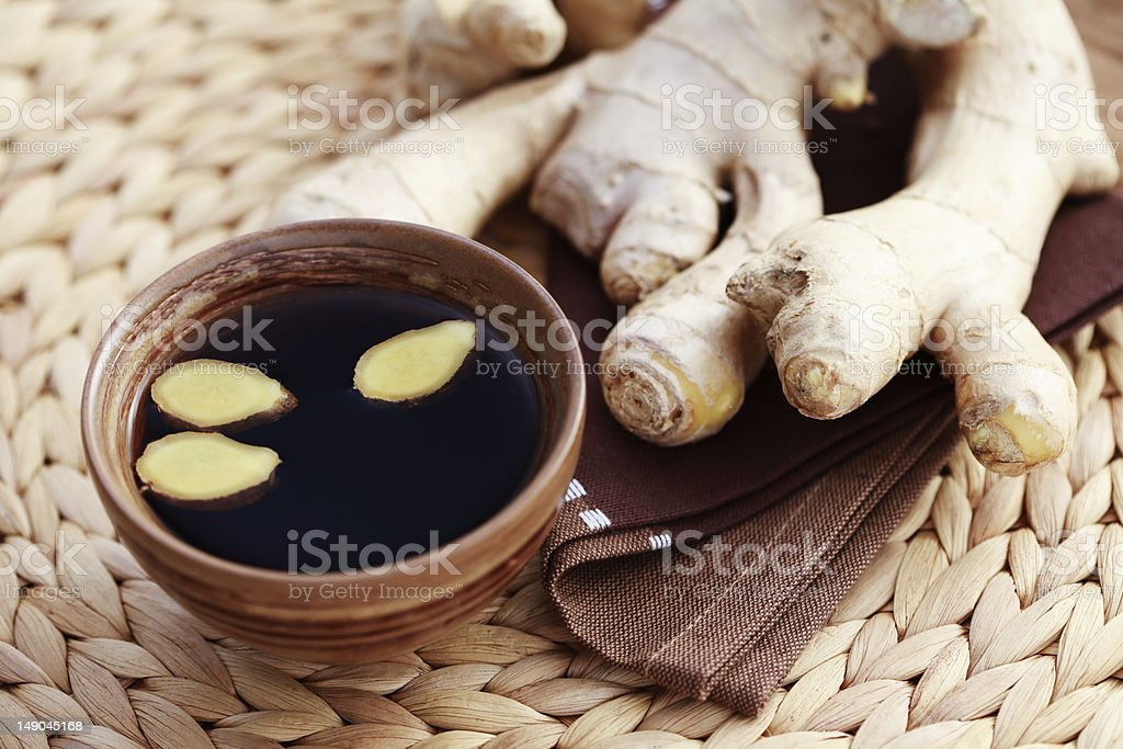 Brown cup of ginger tea next to roots stock photo