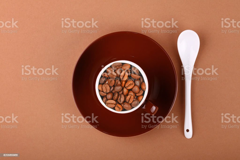 Brown cup of roasted coffee beans on parchment stock photo
