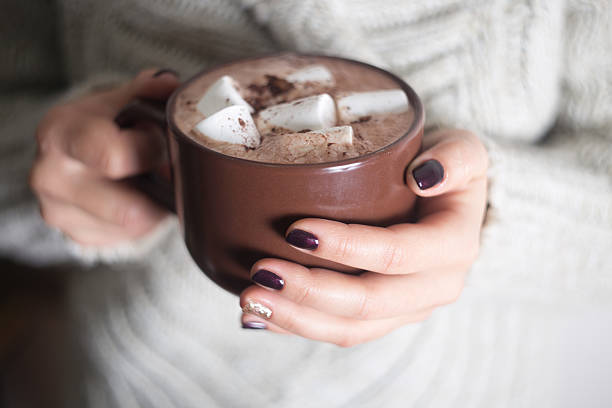 brown cup with cocoa and marshmallow in the hands - hot chocolate stock photos and pictures