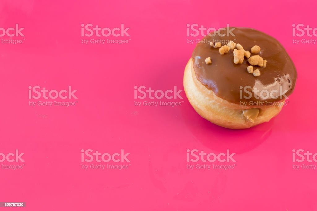 Brown donut on pink background stock photo