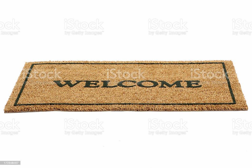 Brown door mat with welcome written across in black stock photo