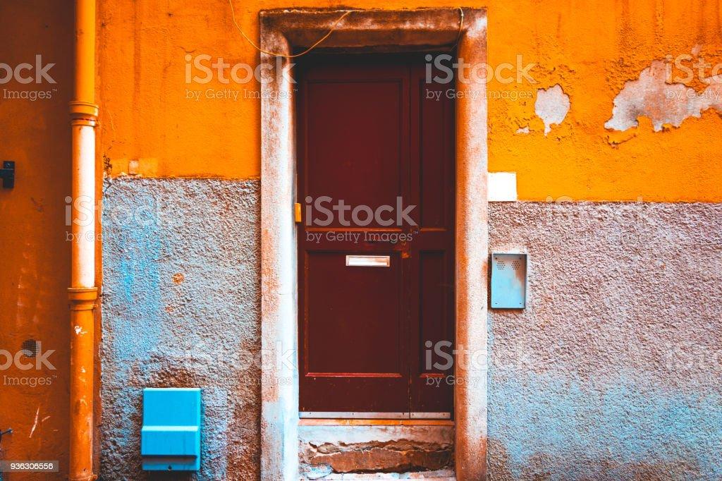 brown door on orange colored building stock photo
