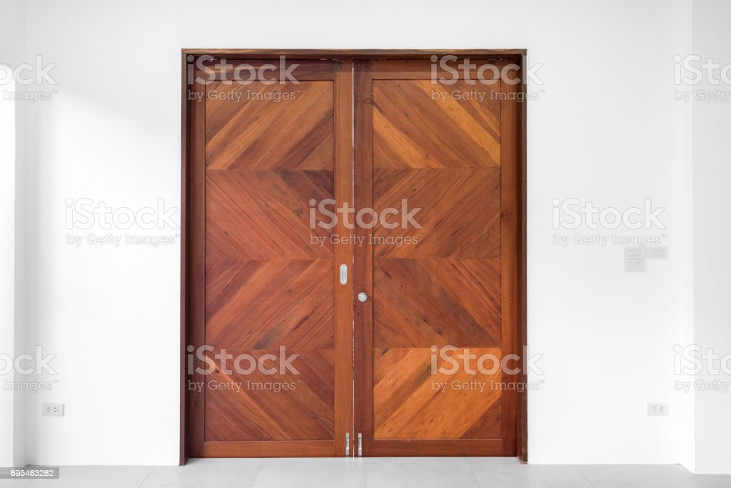 Brown double wood door on white wall background stock photo