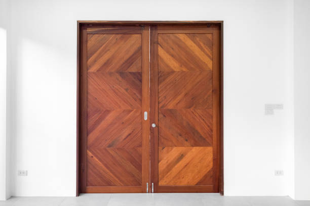 brown double wood door on white wall background - symmetry stock photos and pictures