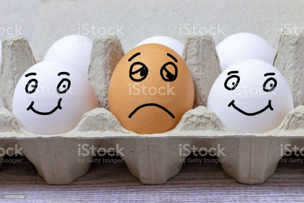 Brown egg with face expression of sad between two white happy eggs.