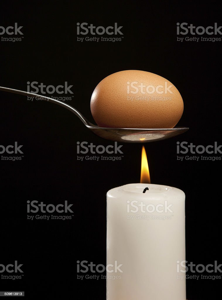 Brown egg wrapped in smoke in silver spoon stock photo