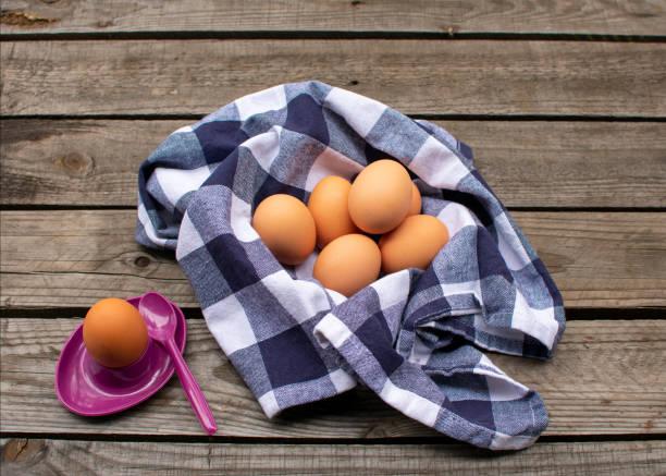 braune Eier in einer blau-weiß karierten Serviette, daneben ein Ei in einem lila Eierbecher. – Foto