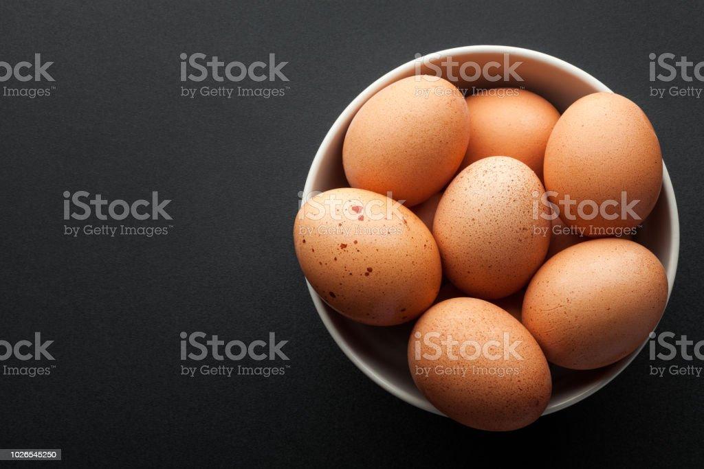 bruine eieren in kom geïsoleerd op donkere achtergrond. bovenaanzicht - Royalty-free Biologisch Stockfoto